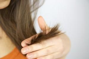 Девушка держит между пальцев волосы