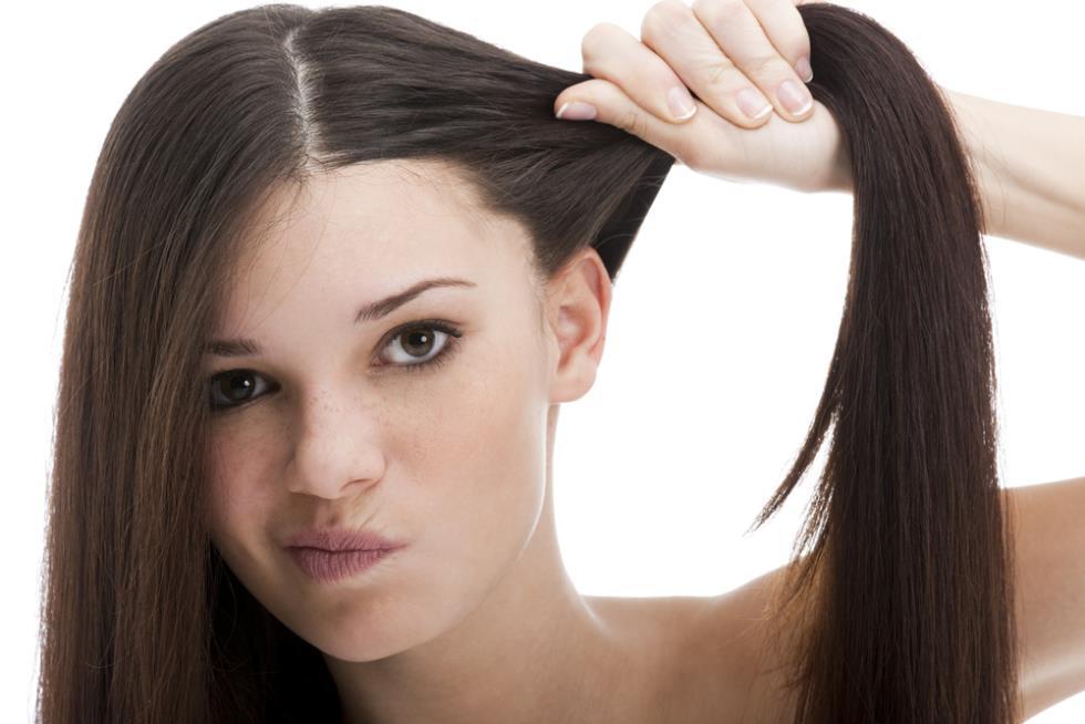 Девушка держит в кисти свои волосы