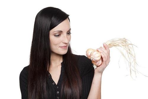 Девушка держит в руке чеснок