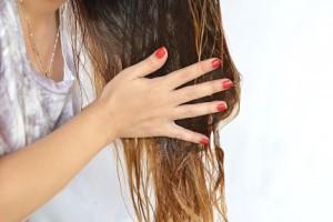 Девушка наносит бальзам на волосы