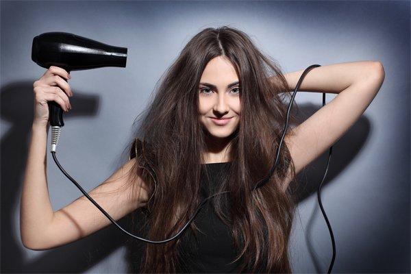 Девушка сушит волосы феном