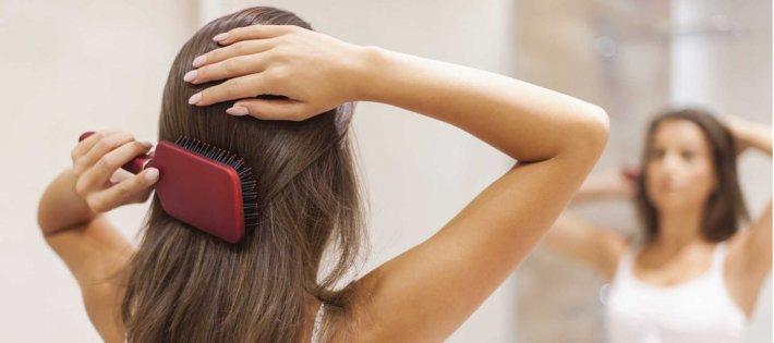 Девушка смотря в зеркало расчесывает волосы