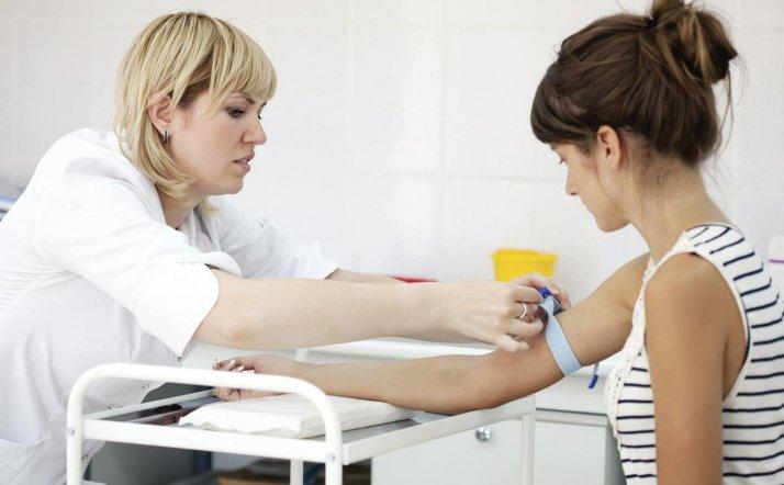 У девушки медсестра берет кровь с вены