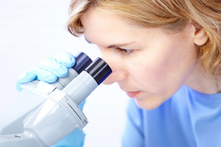 женщина смотрит в микроскоп
