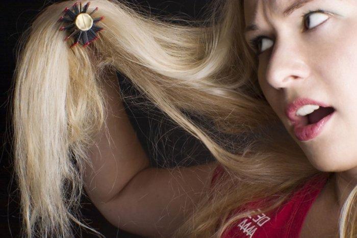 Девушка расчесывает секущиеся волосы