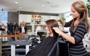 Парикмахер стрижет волосы девушки