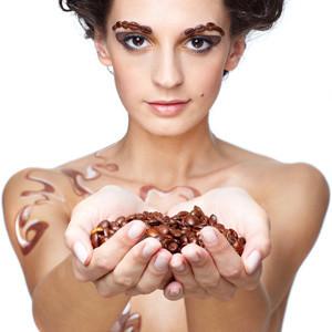 Девушка в руках держит кофейные зерна