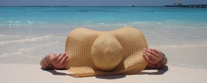 Девушка в шляпе загорает на море