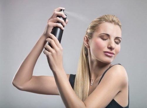 Девушка наносит спрей для волос