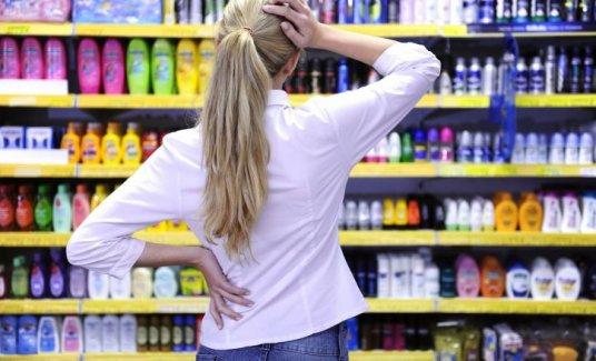 Девушка выбирает в магазине краску для волос