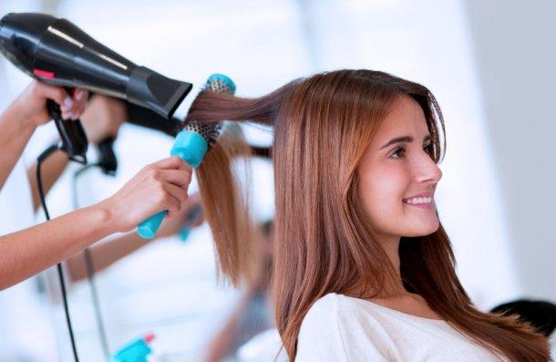 Девушки в салоне сушат волосы феном
