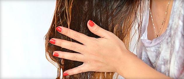 Девушка держит в руках свои волосы