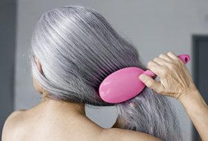 Женщина расчесывает седые волосы