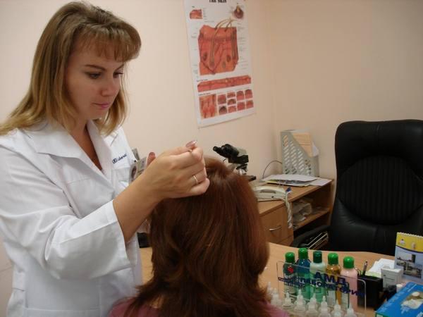 трихолог рассматривает волосы у девушки