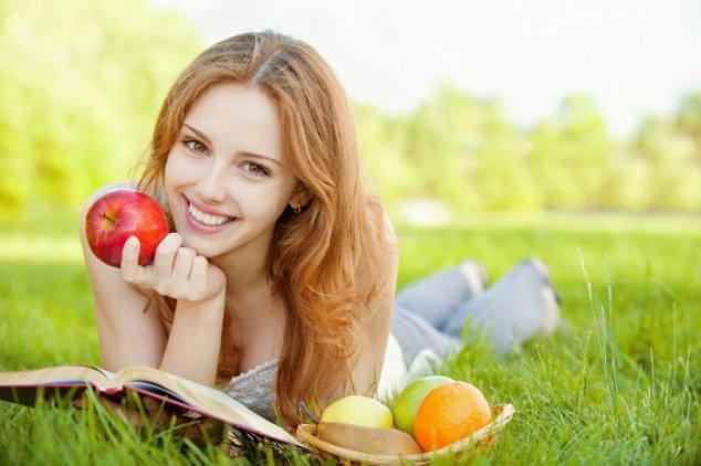 Девушка лежит на траве с яблоками